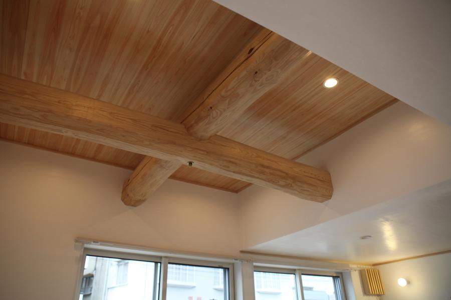 北欧テイストの白い壁と白い天井に丸太組みのある自然素材の木の家の画像