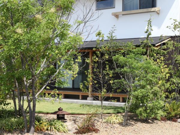 ナチュラルな自然素材の木の家の芝生と雑木林風のガーデニング