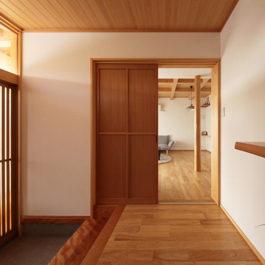 ナチュラルな自然素材の木の家の注文住宅の玄関とリビング