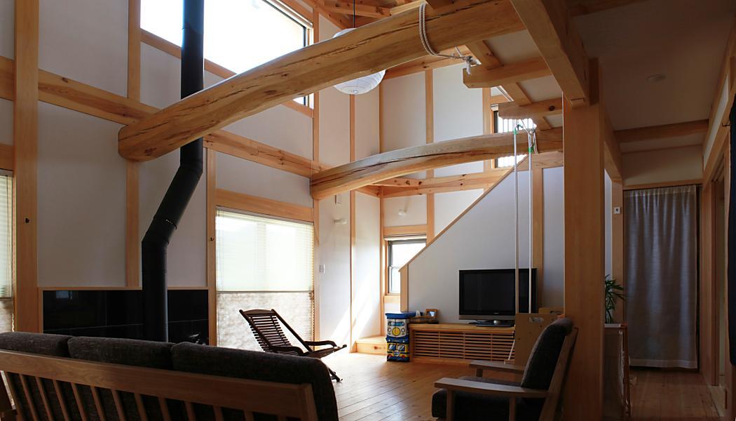 自然素材による別荘風の木の家の大きな吹き抜けと薪ストーブのあるリビング空間