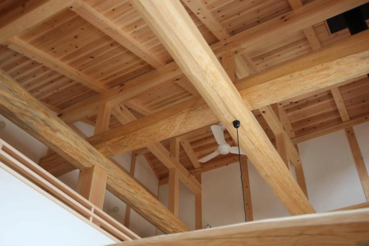 大きな吹き抜けのある自然素材による木の家の上部の丸太組みを見上げた画像