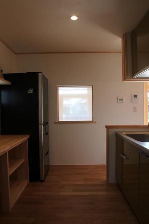 玄関が覗ける四角い窓のある自然素材による木の家のキッチン(kitchin)廻り