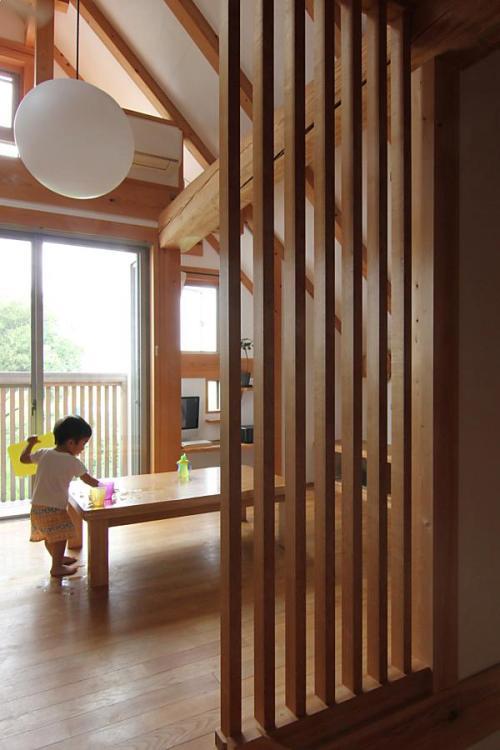 愛知県でカフェ(cafe)スタイルの自然素材の小さな木の家の格子越しに見たリビングダイニング