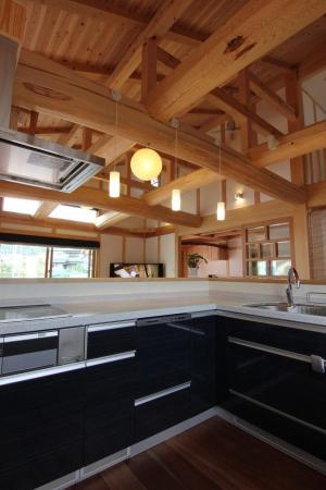 豪快な丸太組みに囲まれた自然素材による木の家のL型キッチン(kitchin)