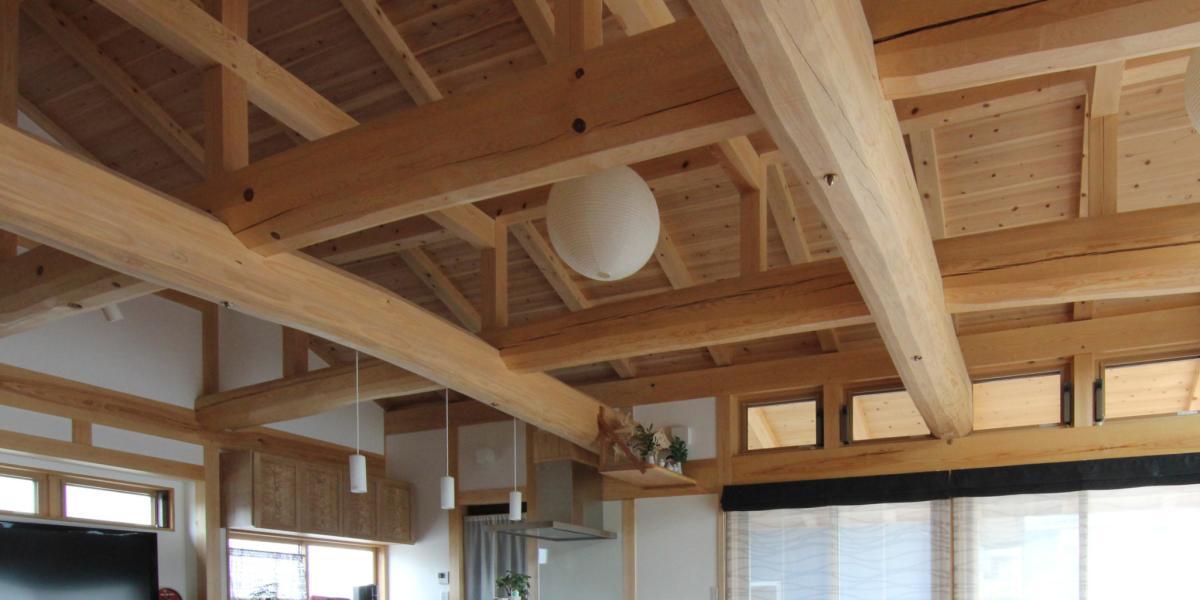 自然素材による大空間の大きくて豪快な丸太組みの下からの画像