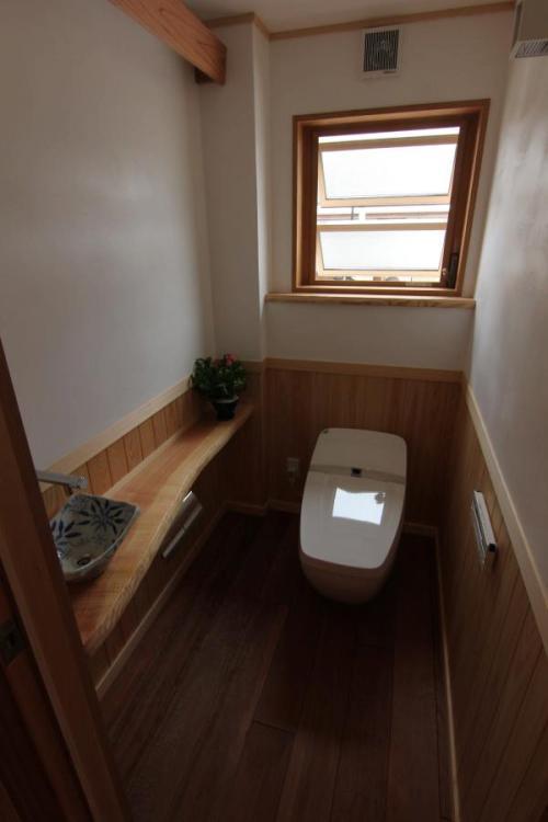無垢の木製カウンターと腰板のある自然素材による木の家のトイレ(便所)