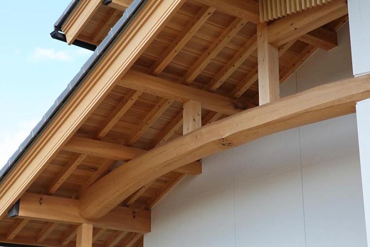 燻し瓦の瓦屋根を葺いた純和風の家の外部の丸太を表わしにした画像