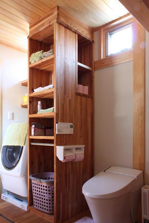 脱衣室と一体で収納力のある棚のある、自然素材による木の家のトイレ(便所)